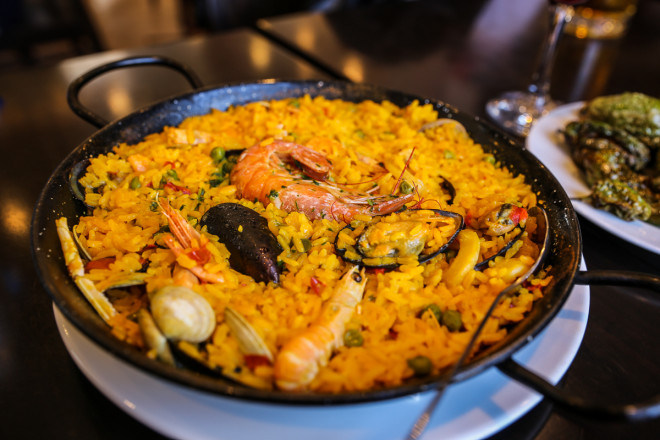 Seafood Paella Paella is a Valencian rice dish that originated in its modern form in the mid-19th century near lake Albufera, a lagoon in Valencia, on the east coast of Spain. Many non-Spaniards view paella as Spain's national dish, but most Spaniards consider it to be a regional Valencian dish. Valencians, in turn, regard paella as one of their identifying symbols.